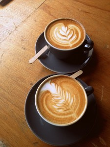 Two coffees with traditional latte art leafs on their surfaces in dark cups on matching saucers