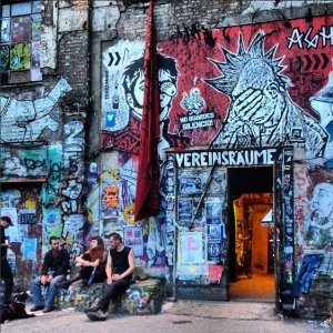 Exterior of a squat house adorned with graffiti and street art in Berlin with three young people sitting in front and chatting