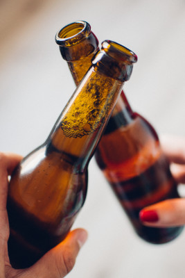two bottles of beer clinking cheers