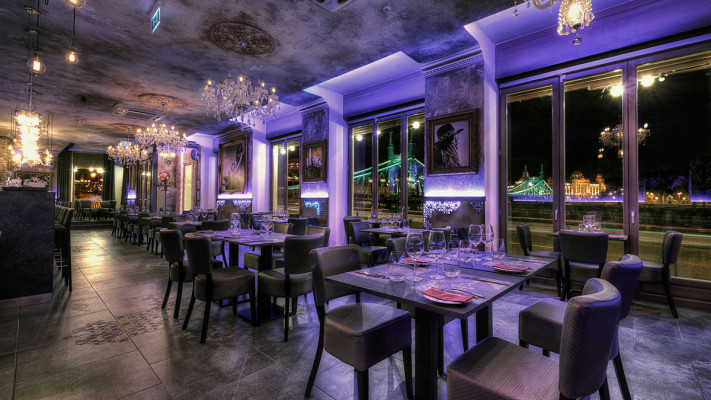 interior of romantic restaurant in Budapest with views of the Danube river at night