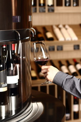 A customer pouring red wine from tap in CultiVini wine shop and wine bar in Budapest