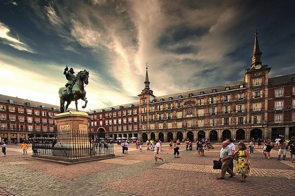 daytime at Plaza Mayor in Madrid as tourists stroll around the equestrian statue of Carlos III