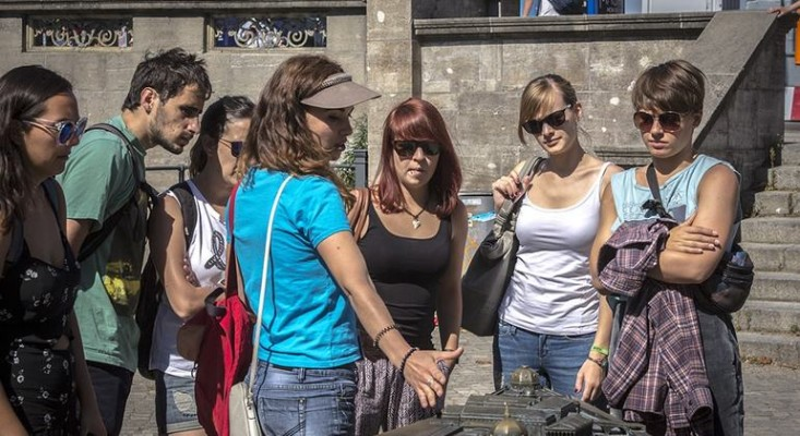 A Berlin city tour guide showing her group of tourists a point of interest on a free walking tour in Berlin