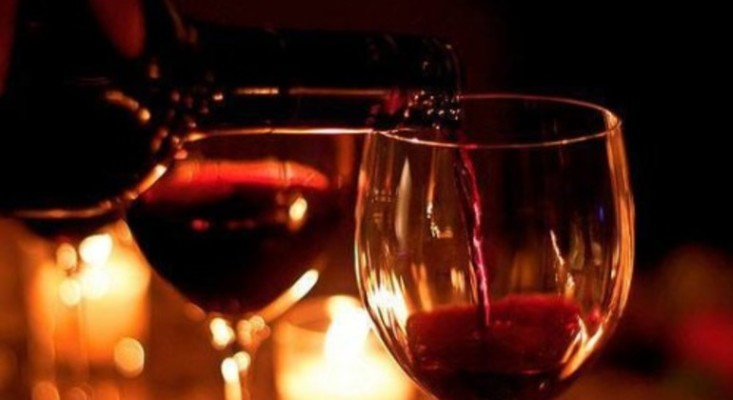 Two half-filled glasses of red wine on a dark wood table surface, illuminated by the soft glow of candle light
