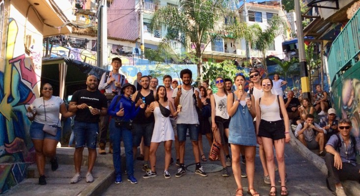 a free tour group of young tourists in Communa13 enjoying local lime ice cream with their walking tour guide in front of barrio graffiti