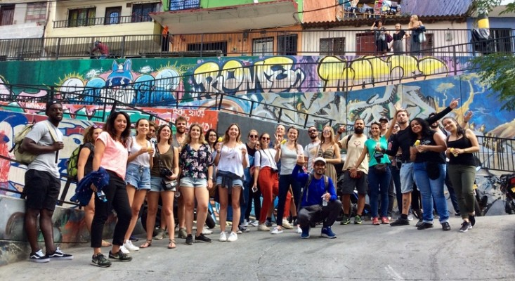 group of young happy tourists with a local tour guide in the communa 13 barrio of Medellin in Colombia on a sunny day during a free walking tour with graffiti in the background