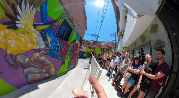 urban art and graffiti in communa 13 in Medellin being shown to a group of tourists by their local tour guide