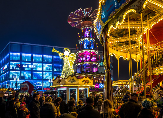 the christmas market at Alexanderplatz in Berlin, Germany, with festive lights and Christmas decorations at night while people explore the stalls