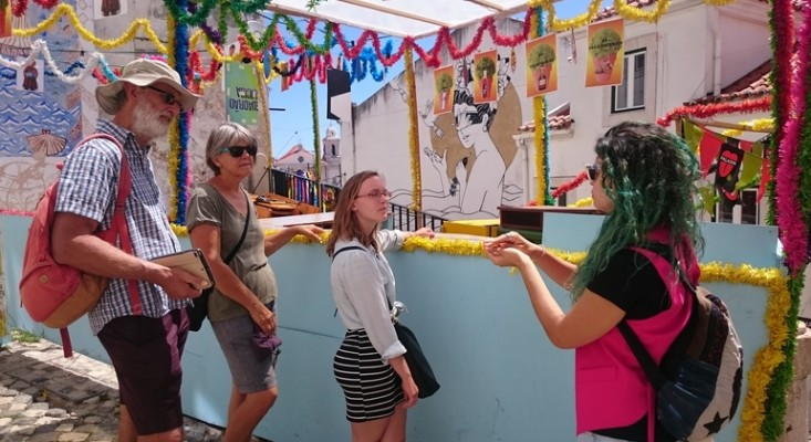 A walking tour guide in Alfama, Lisbon, showing tourists the murals and colourful bunting and urban art of the area on a bright sunny day.