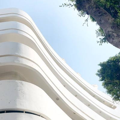 the curves and rounded corner of a 1930's era multi-storey Bauhaus building in the White City, Tel Aviv, Israel