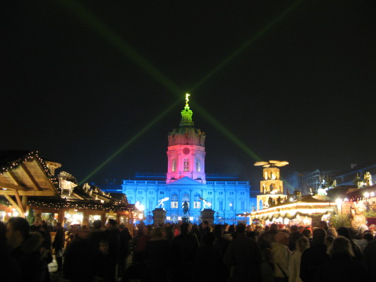 People shopping and browsing at Christmas market at Charlottenburg in Berlin at night with the palace illuminated in white, green, and pink lighting in the background