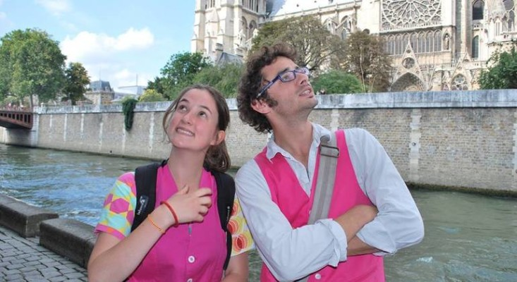 Two young Paris city walking tour guides, a boy and girl, posing in front of Notre Dame cathedral in Paris