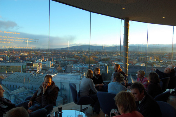 People drinking in The Gravity Bar in The Guinness Storehouse, Dublin, with a clear view out across the Dublin skyline