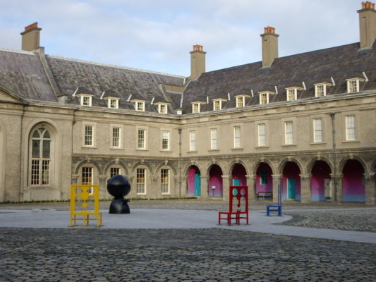 Courtyard of IMMA Art gallery in Dublin including art installation consisting of large chairs coloured in yellow, red, and blue and a black pawn shaped sculptor with bulbous head