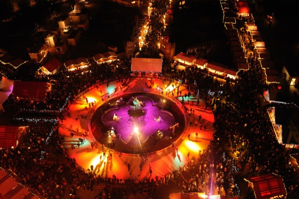 Ice skating rink in Alexanderplatz from above, illuminated in purple and orange with skaters on the ice and crowds of people watching