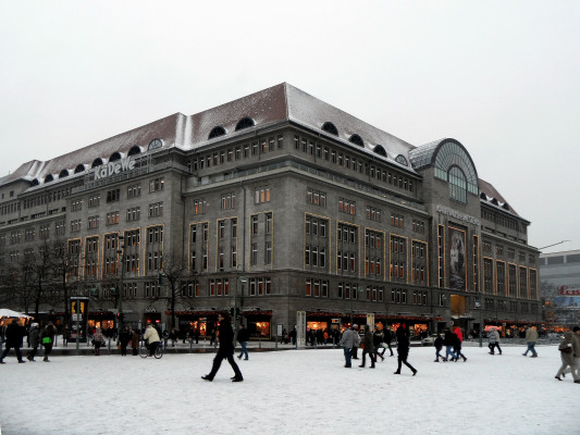 Exterior of the KaDeWe shopping centre in Berlin, Germany at daytime with snow on the groupnd and people passing by