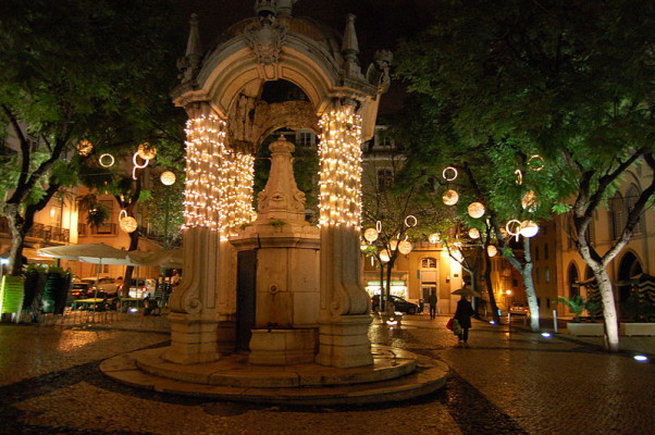 Largo do Carmo fountain, Lisbon, at night and decoreated with multiple small lights around its columns and hanging lanterns