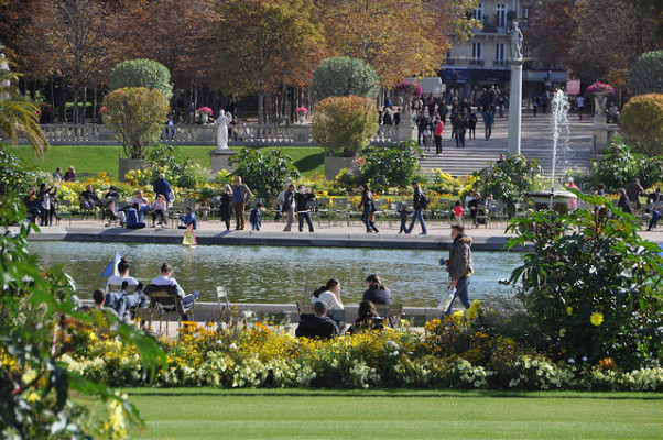 Part of the Luxembourg Gardens in the Left bank of Paris, with people sitting on benches, walking around the pond in the centre, and manicured trees and shrubs in the background
