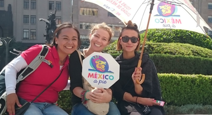 a free walking tour guide with two tourists, one holding a free tour branded dign, and the holding a city tour branded umbrella, in Mexico City