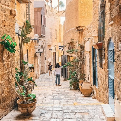 two pedestrians on a winding narrow alley path in Old Jaffa, Tel Aviv, Israel
