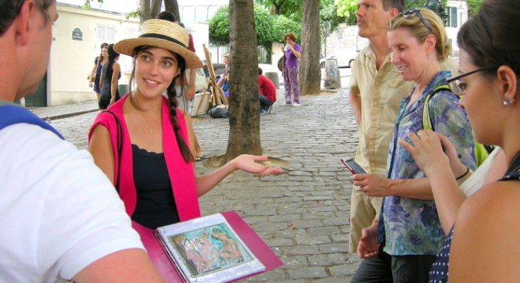 A city tour guide conducting a free walking tour in Paris, France, surrounded by some tourists