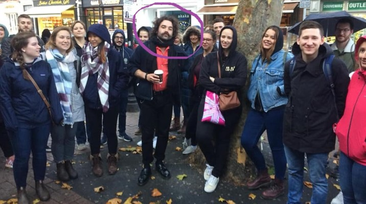Group of tourists on a free walking tour in Dublin with their city tour guide who is a hipster