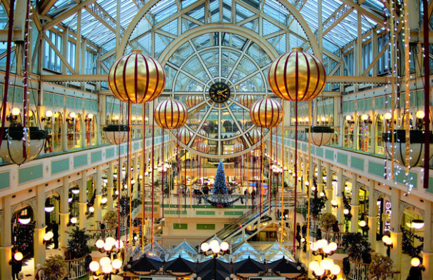 Elevated view of the interior of St. Stephen's Green Shopping Centre in Dublin, Ireland, with Christmas decorations and clock hanging from glass ceiling