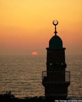 The sun setting on the Mediterranean sea on Tel Aviv's west coast, with the silhouette of a tower in view