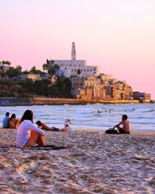 people relaxing on the sand on Tel Aviv beach at sunset while people swim in the water in sight of the city buildings