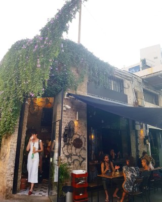 Ivy covered corner-cafe front in Tel Aviv, Israel, with people sitting outside on the street-side terrace drinking coffee and a female customer exiting