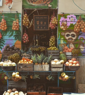 A selection of colourful fresh fruit on display in front of a street juice bar, decorated with colourful painted pictures of a monkey, in Tel Aviv, Israel