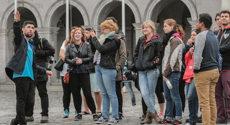 A group of tourists with a tour guide on a free walking tour in Dublin city