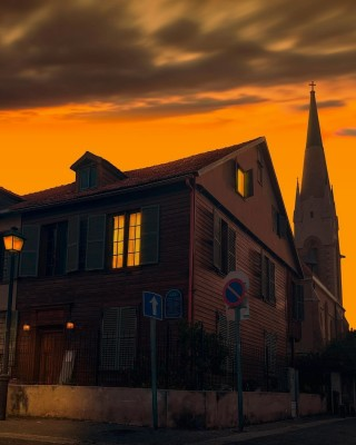 Golden sky at sunset over church steeple and wooden two storey house in Tel Aviv