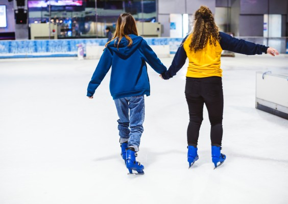 Two girls ice-skating on an indoor ice rink