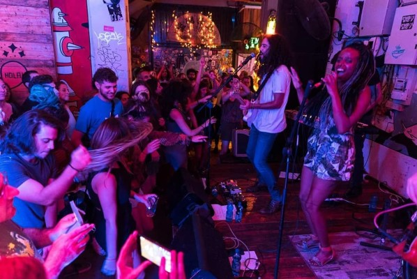 Live band performing at a bar on a small stage in Tel Aviv for dancing audience