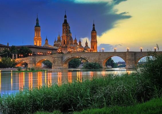 Basilica del ilar in Zaragoza illuminated with lights at sunset