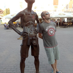 The man who started Zaragoza free walking tour in Zaragoza, Spain, standing beside a statue in the city