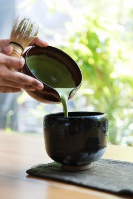 green antioxidant beverage poured from a bowl to another bowl