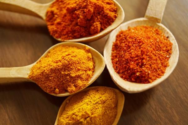 four spoons, each with a spice - turmeric, cinnamon, chilli powder, cayenne