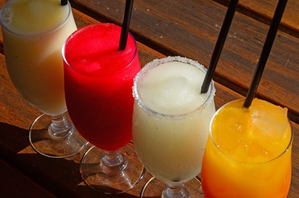 four cocktails of different fruit flavours in a row