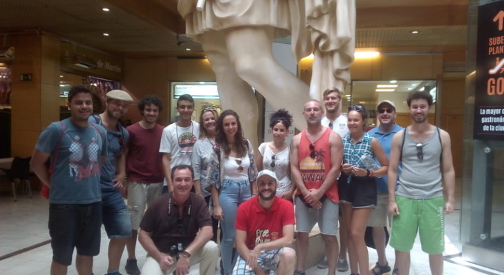 A group of tourists taking part in a free walking tour in Zaragoza , Spain, with their free tour guide.