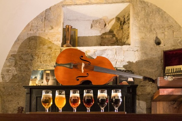Selection of beers ont he bar at Beer Club U Kunstatu in Prague with Viola and stone wall in background