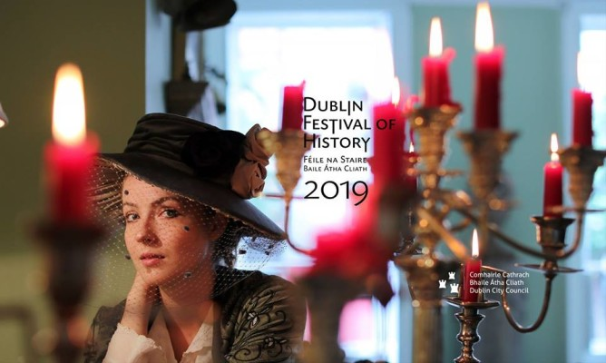 woman in traditional old garb and hat beside tier of candles and information promoting Dublin festival of History 2019
