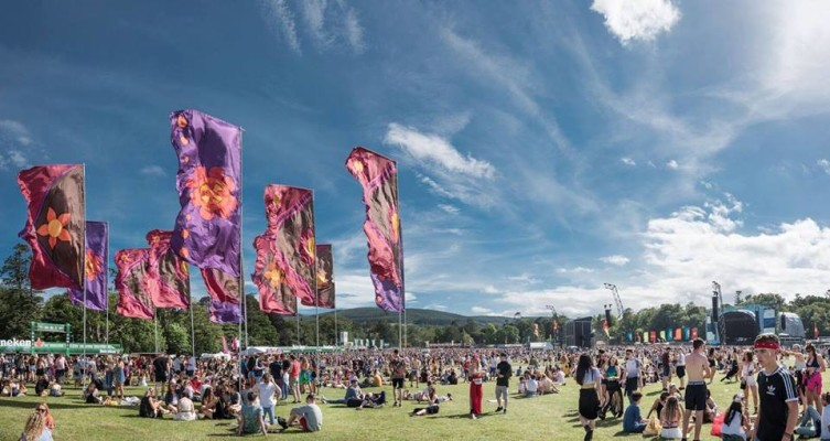 crowd of young people and large flags under blue sky at Longitude Festival in marley park in Dublin, Ireland