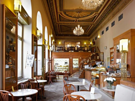 Interior of Cafe Savoy, Prague, with high ceilings, chandeliers and traditional Parisian style