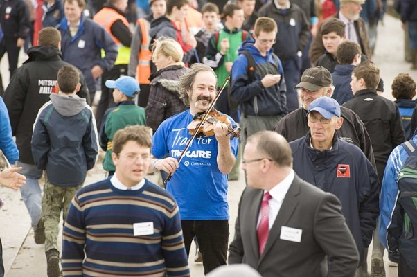 man playing fiddle in a crowd