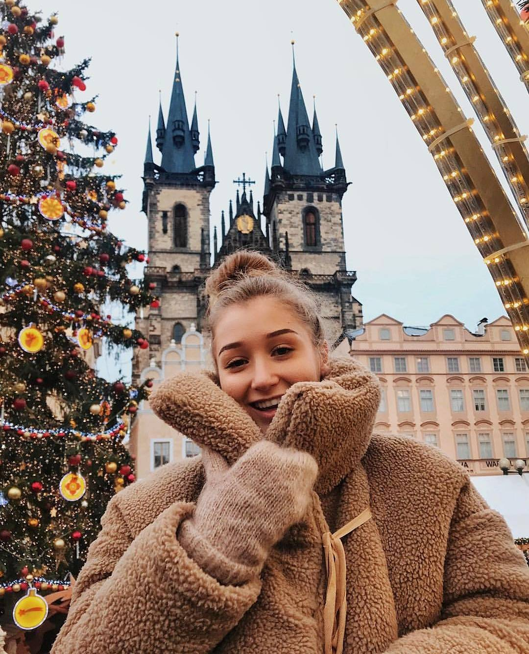 A girl in warm wool cloths and smiling beside a Christmas tree in old town square in Prague in winter