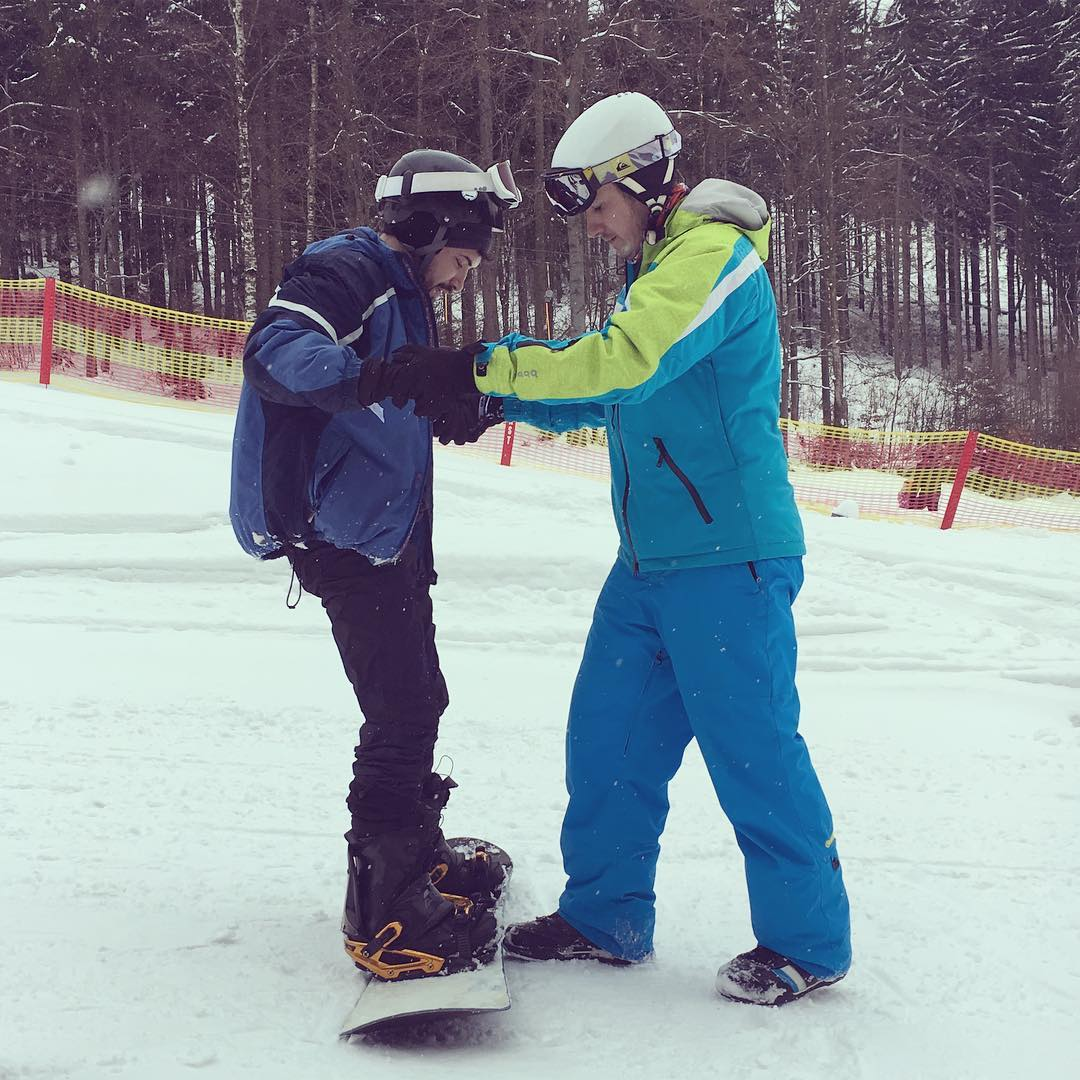 Snowboarder learning to snowboard from ski instructor at Jested ski slope near Prague in winter