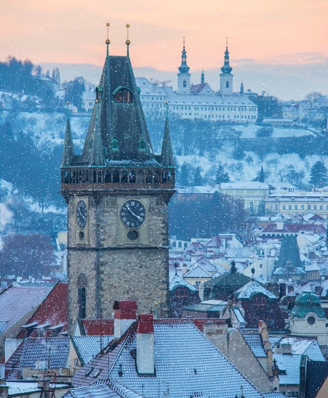 clock tower and rooftops of old town prague covered in snow in winter