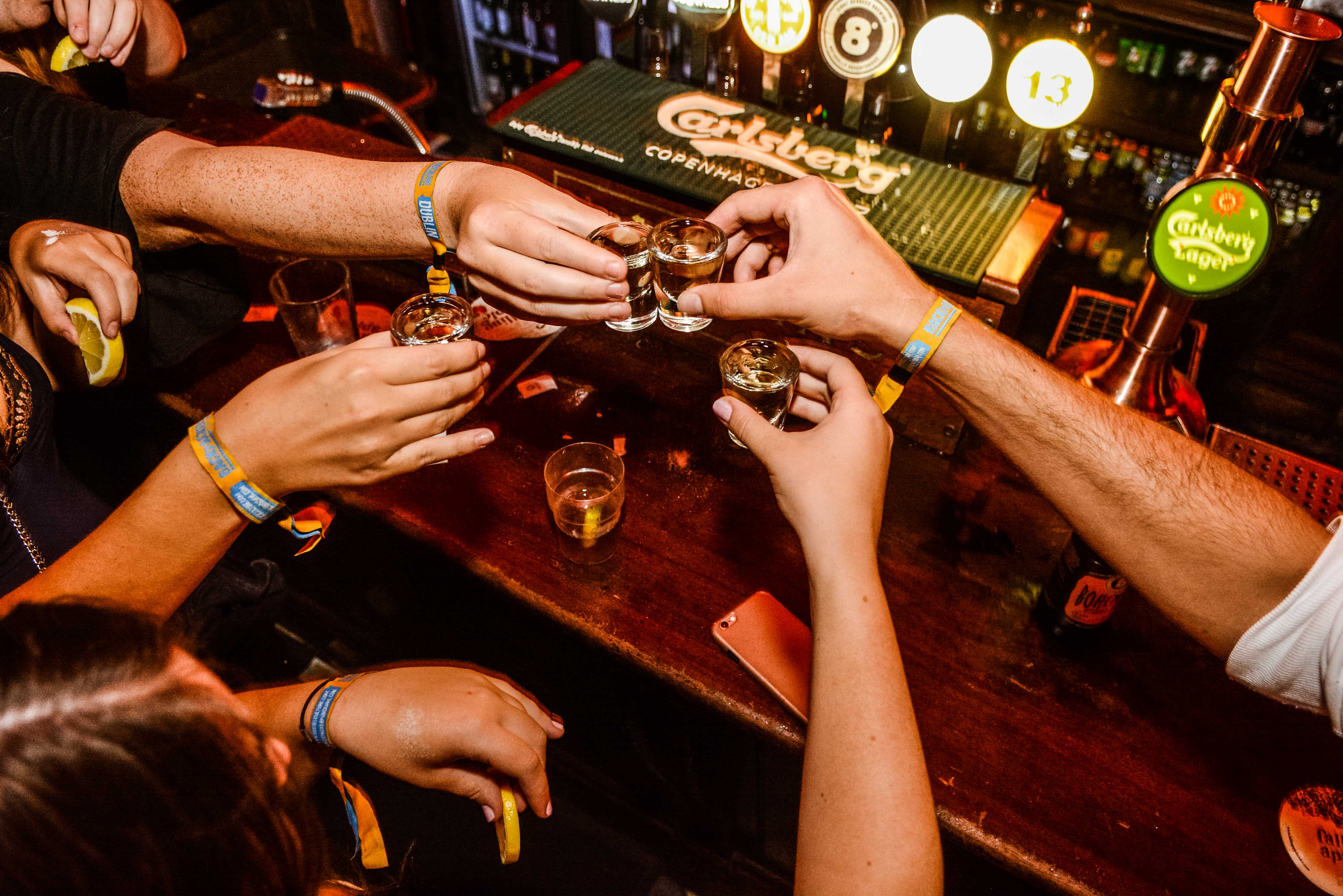 4 people's hands holding free shots and wearing Dublin pub crawl wristbands on a bar crawl in Dublin